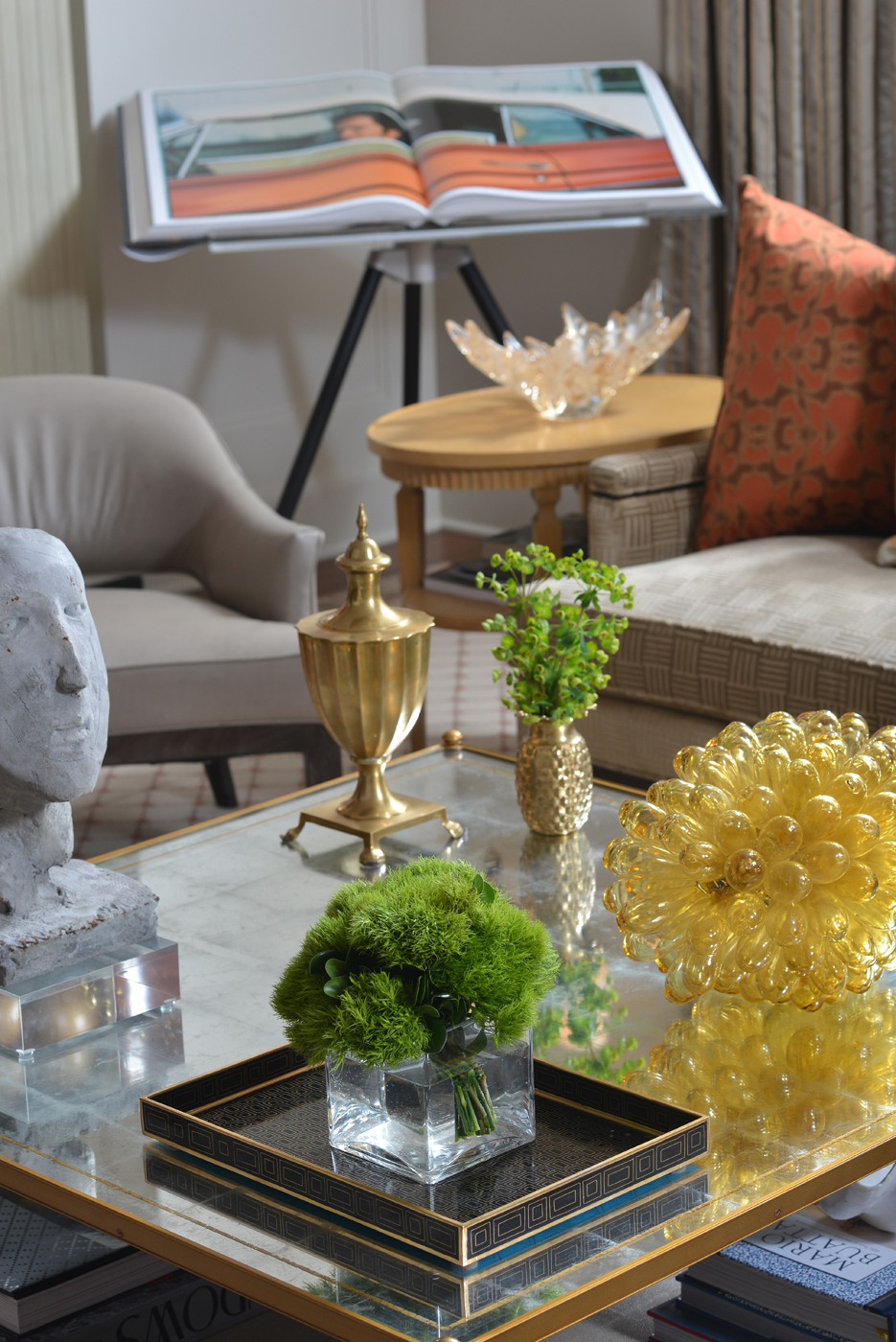 Gilt metal coffee table with mirror top displays a collection of sculptures and decorative objects | Savage Interior Design
