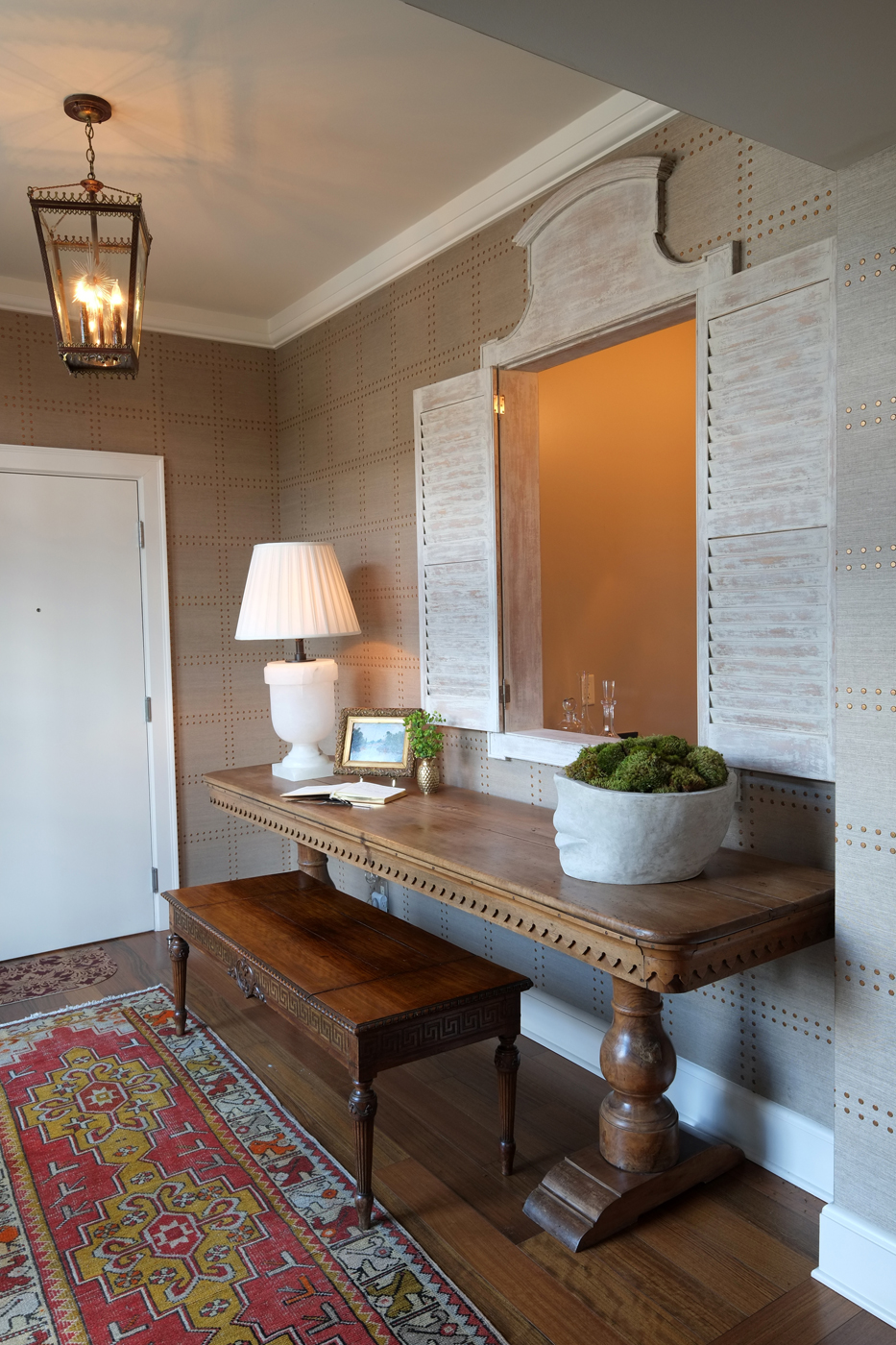 Console table paired with bench and distressed painted shutters flanking an opening to a bar | Savage Interior Design