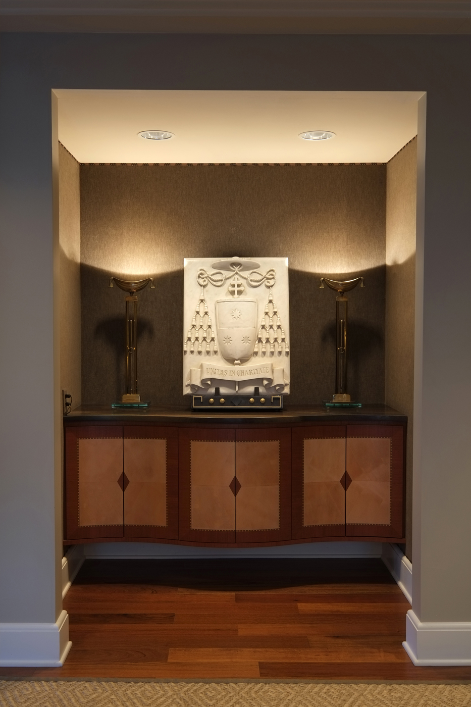 Art deco style cabinet and pair of torchieres surround a bas-relief sculpture coat of arms | Savage Interior Design