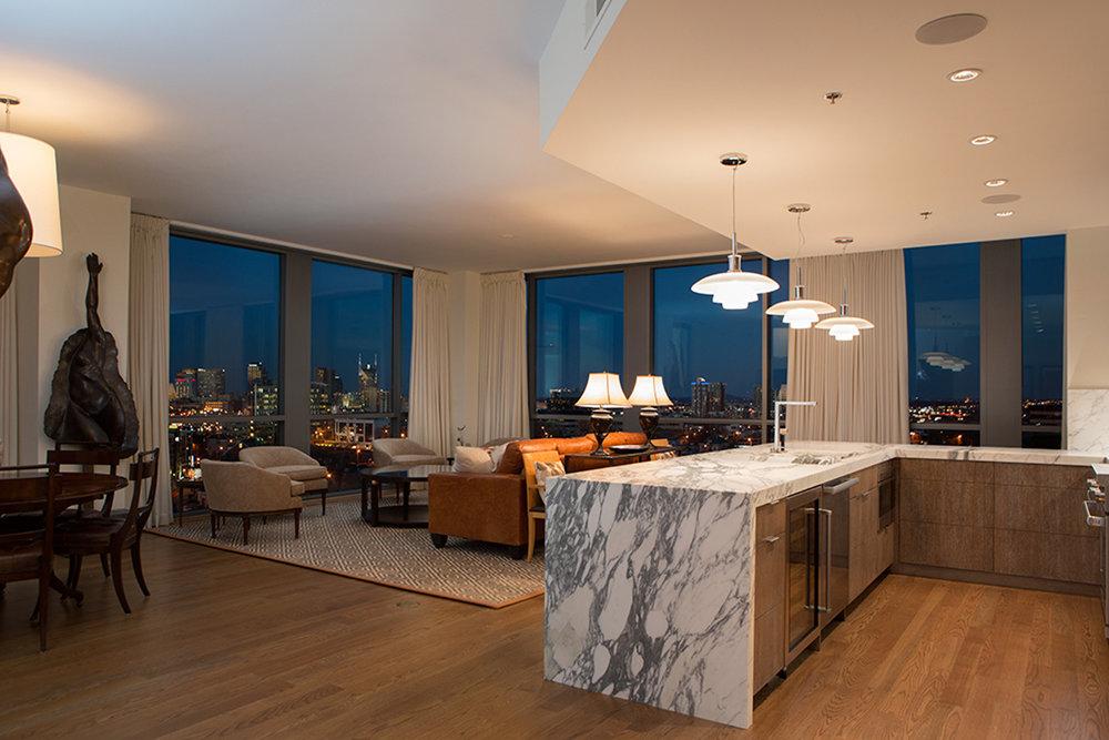 Henningsen style pendants and Calacatta white and gray marble waterfall kitchen countertops overlook den | Savage Interior Design