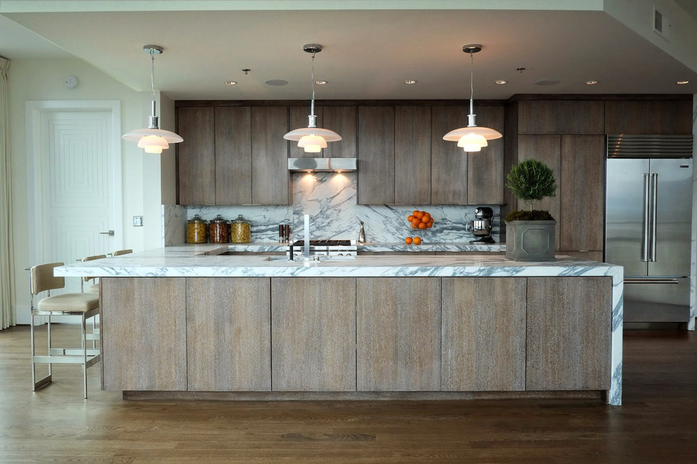 Modern kitchen with cerused gray brown oak cabinetry finish and Calacatta marble waterfall countertop | Savage Interior Design