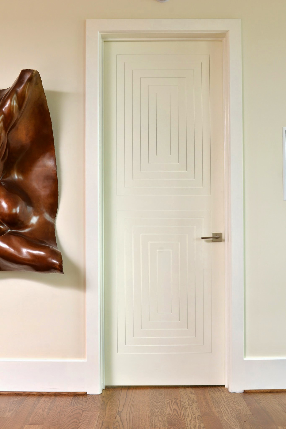 Custom interior door with concentric rectangular box detail and modern sculpture on wall | Savage Interior Design