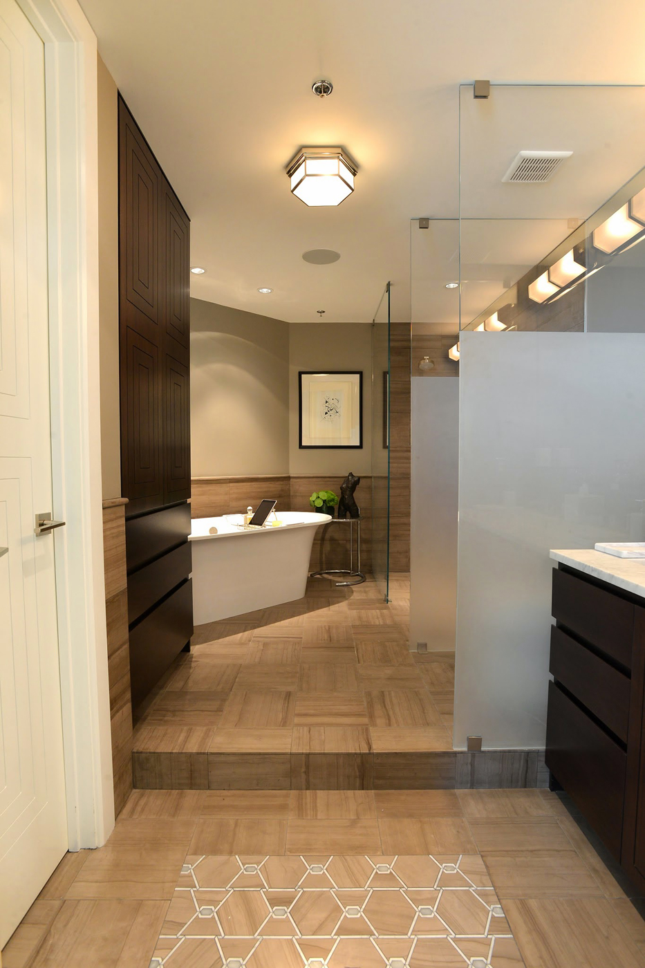 Modern master bathroom with glass panel partitions, strie patterned honed marble floors, and Victoria + Albert bathtub | Savage Interior Design
