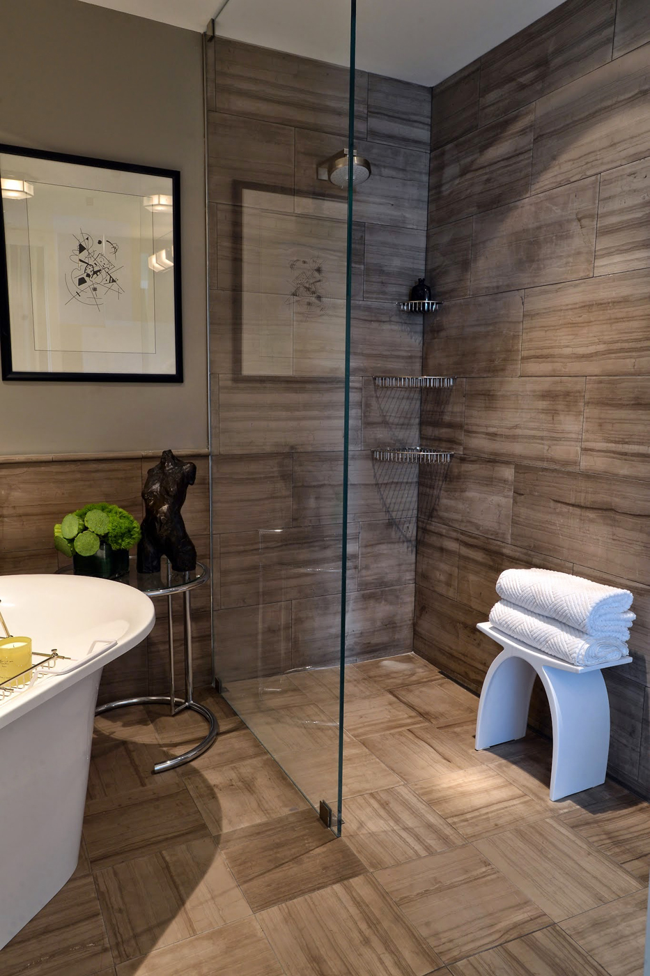 Sleek modern master bathroom glass shower enclosure with brown honed marble tiles in strie pattern | Savage Interior Design