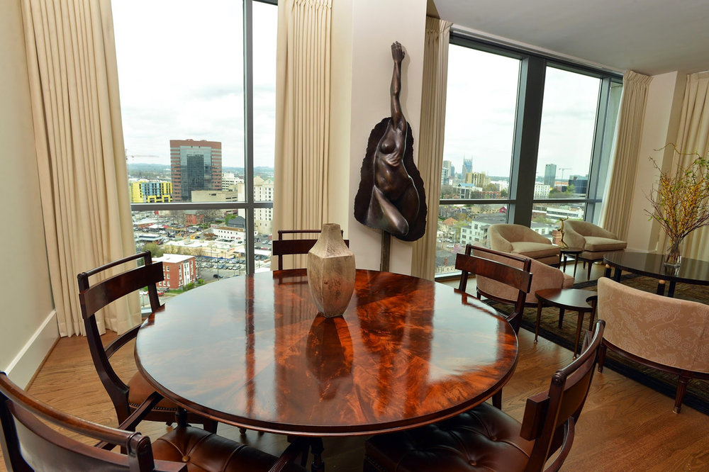 Dining area table with figural wood top and modern sculpture overlooking the Nashville skyline | Savage Interior Design