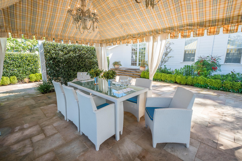 Outdoor dining area under a pair of chandeliers covered by a tent | Savage Interior Design