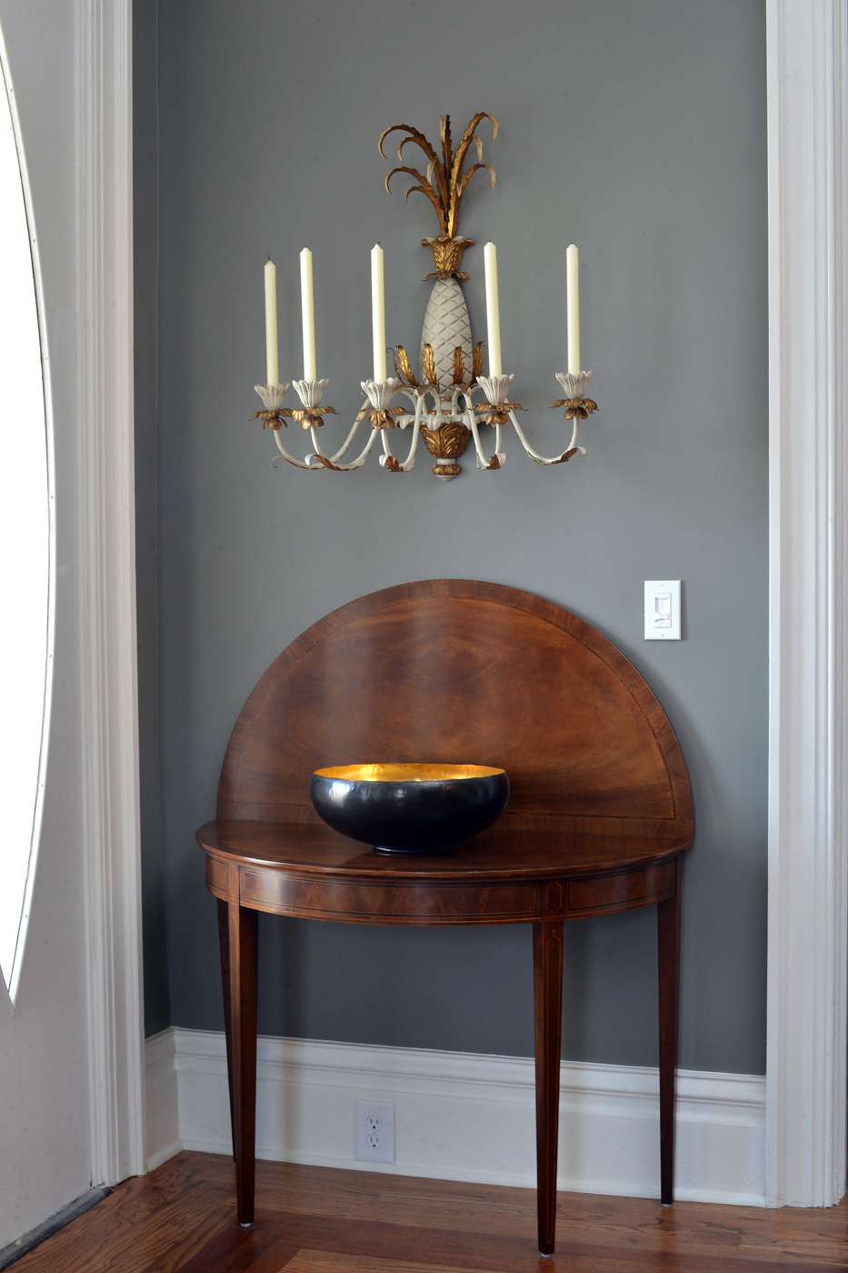 Detail of wooden Hepplewhite style demilune card table in entry room topped by decorative bowl | Savage Interior Design
