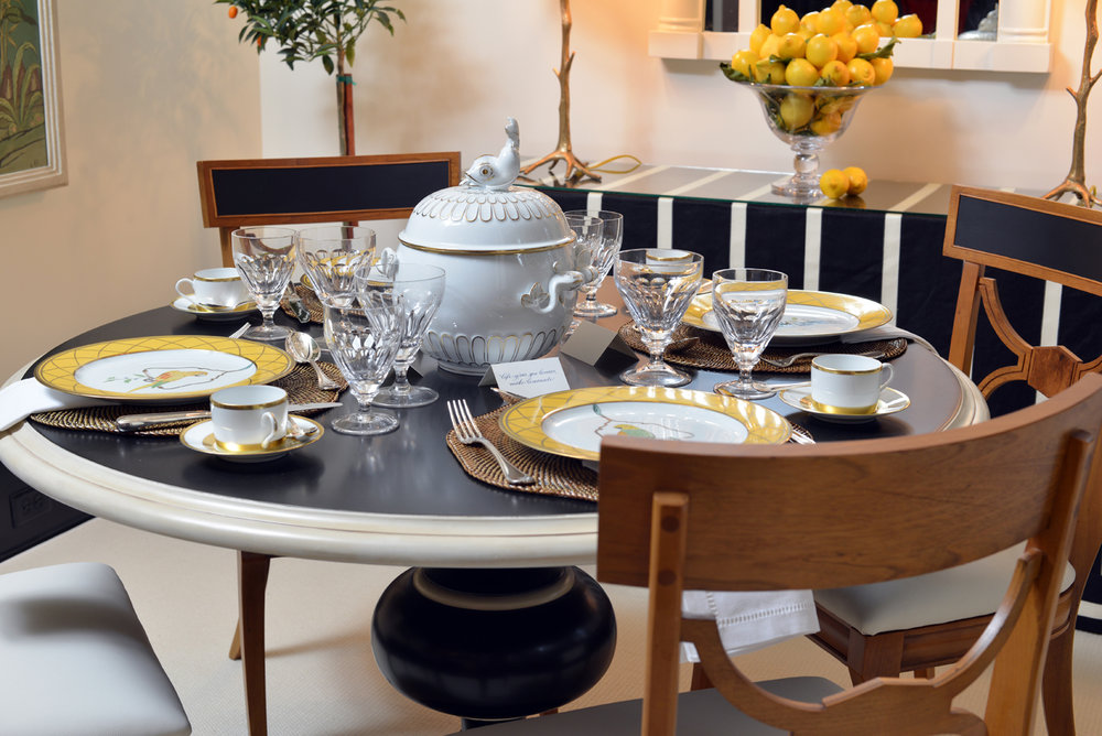 Dining room tabletop with yellow and white china, crystal glassware, and tureen with dolphin finial | Savage Interior Design