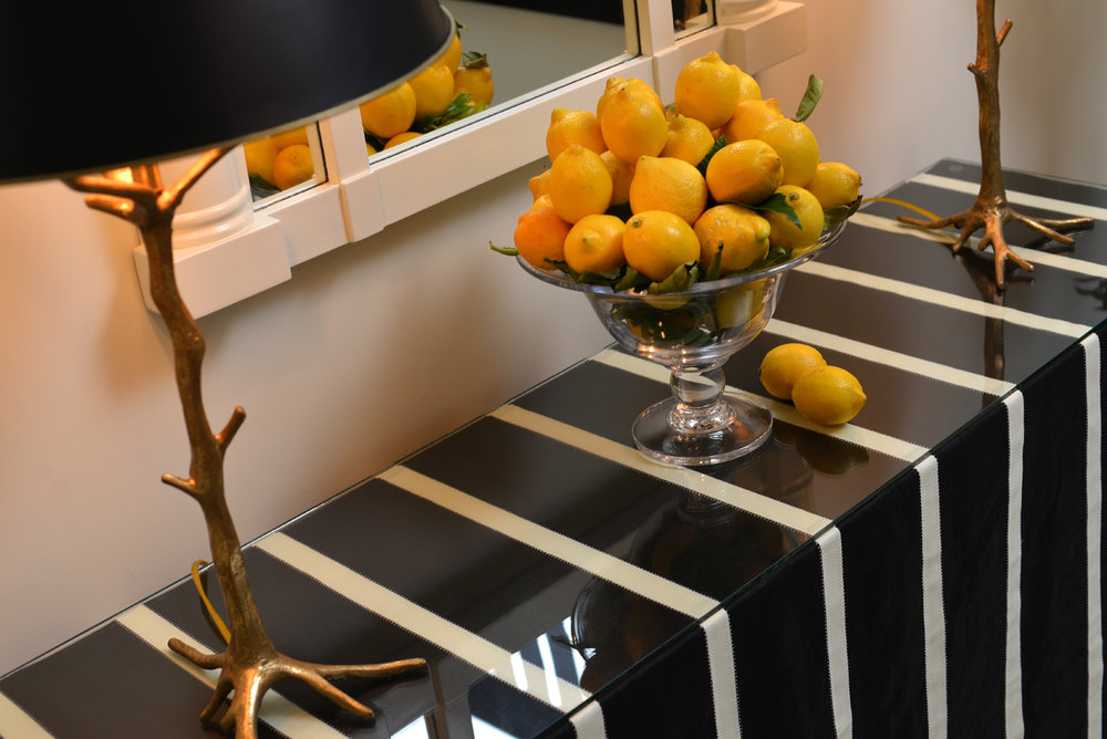 Twig style lamps with bowl of lemons on serving table draped in black and white striped fabric | Savage Interior Design