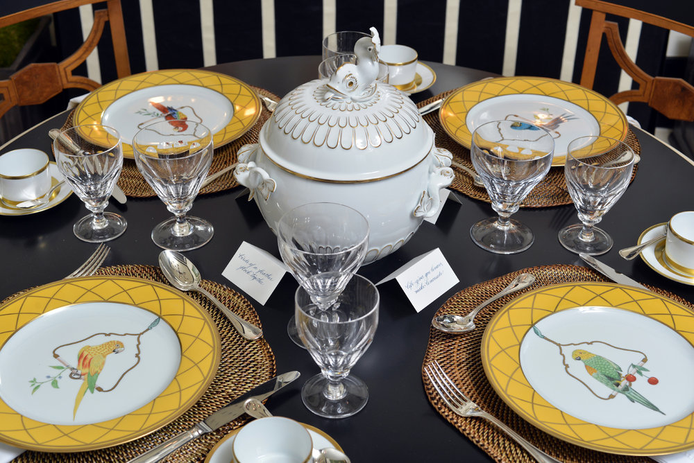 Black tabletop with yellow and white china, crystal glassware, and tureen with dolphin finial | Savage Interior Design