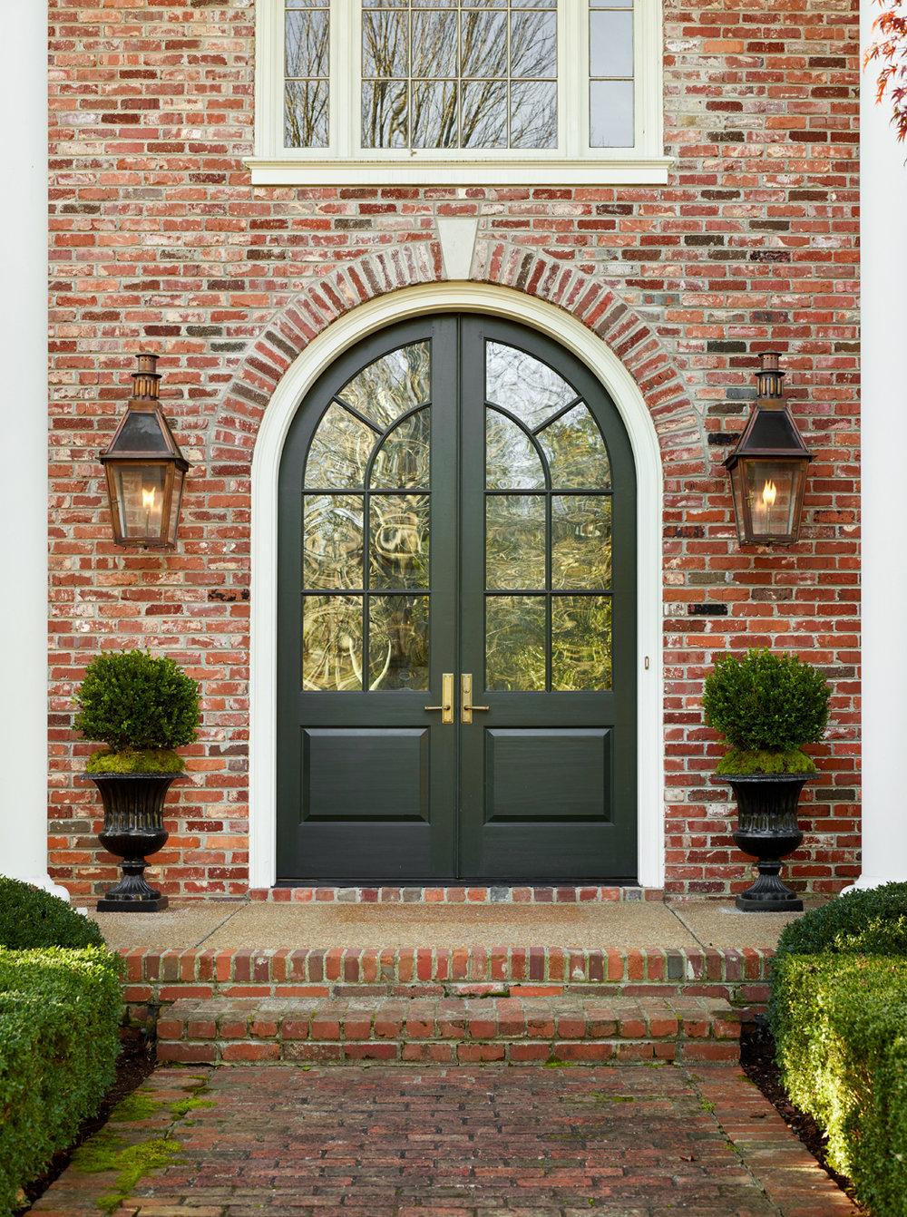 Bevolo copper gas lanterns flanking green Palladian style entry doors on a brick facade | Savage Interior Design