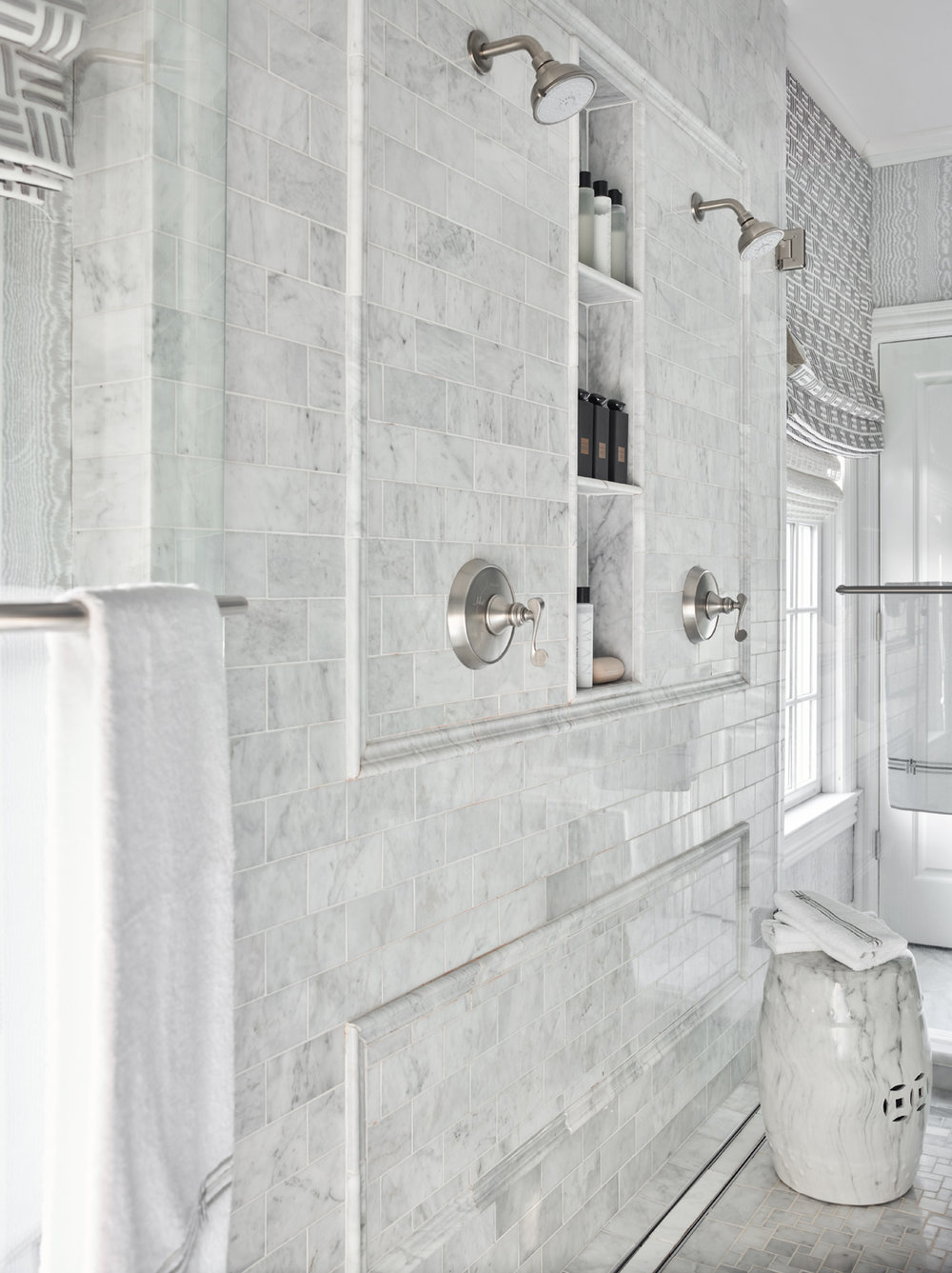 Bathroom shower detail with white marble tiles accented with marble panel molding | Savage Interior Design