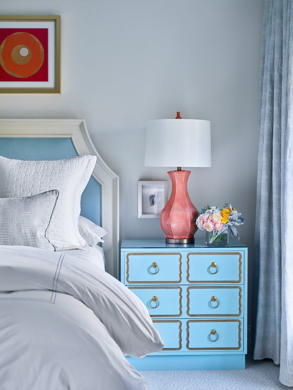 Upholstered blue and white headboard in bedroom; Dorothy Draper Espana chest in blue; coral color lamp | Savage Interior Design