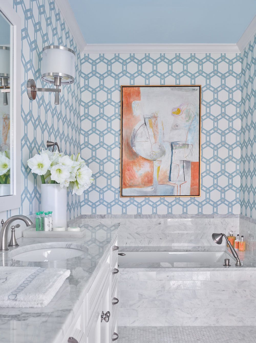 White marble tile floor, tub surround and vanity top in bathroom; blue on white geometric wallpaper with abstract painting | Savage Interior Design
