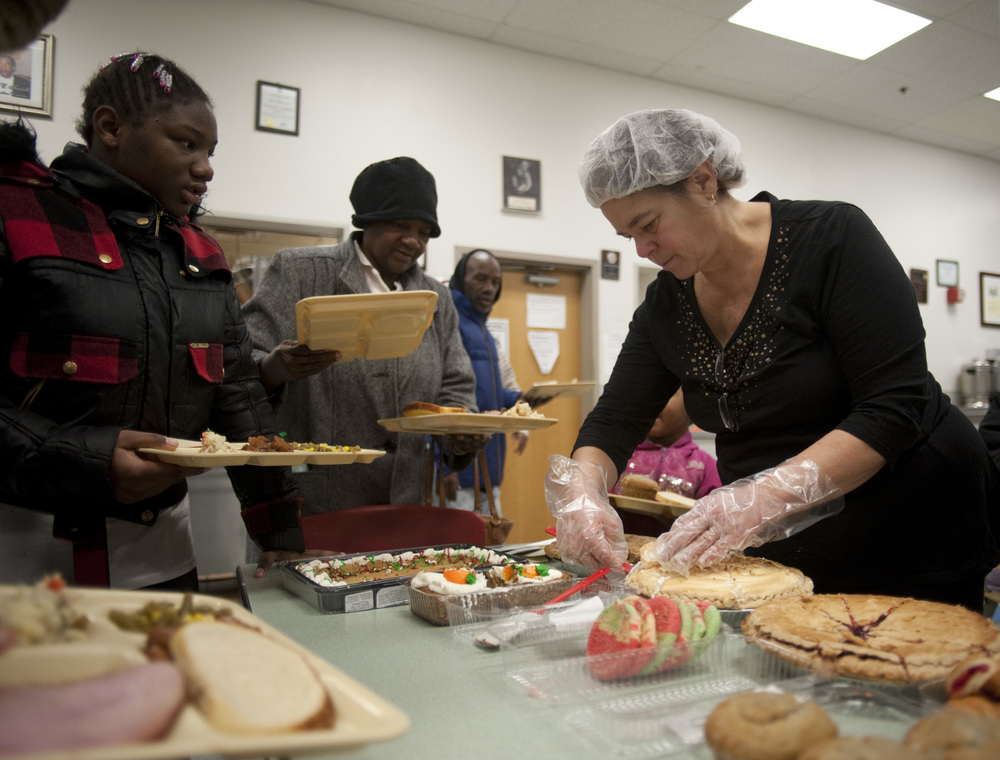 First Grade teacher and first year volunteer Mary Helba serves out dessert to hungry eyes at the Community Kitchen during its annual Christmas food banquet for the homeless.