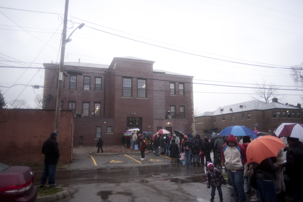 A long line forms early on a rainy December 23rd at the entrance to the Community Kitchen as people wait for the doors to open. For the past 15 years the Community Kitchen has held a Christmas party, giving a free meal and Christmas gifts to the city's less fortunate.