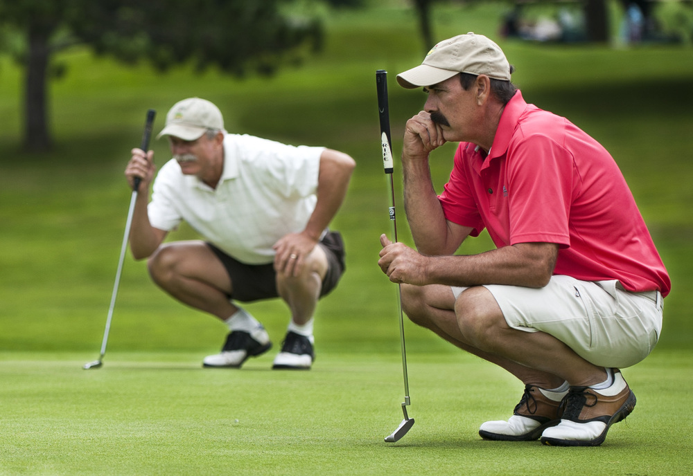 Rory Brown (right) and Dick Meacham (left) each take time to study the putting green during the semi-finals of the City Golf Tournament on Saturday, July 19 at the Edgewood Golf course in Bloomington, Indiana.