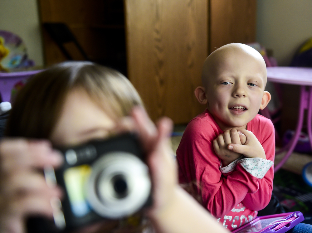 Alexes spent most her days inside as going outside to play was too risky with her weak immune system. Here she watches her younger sister play with a camera.