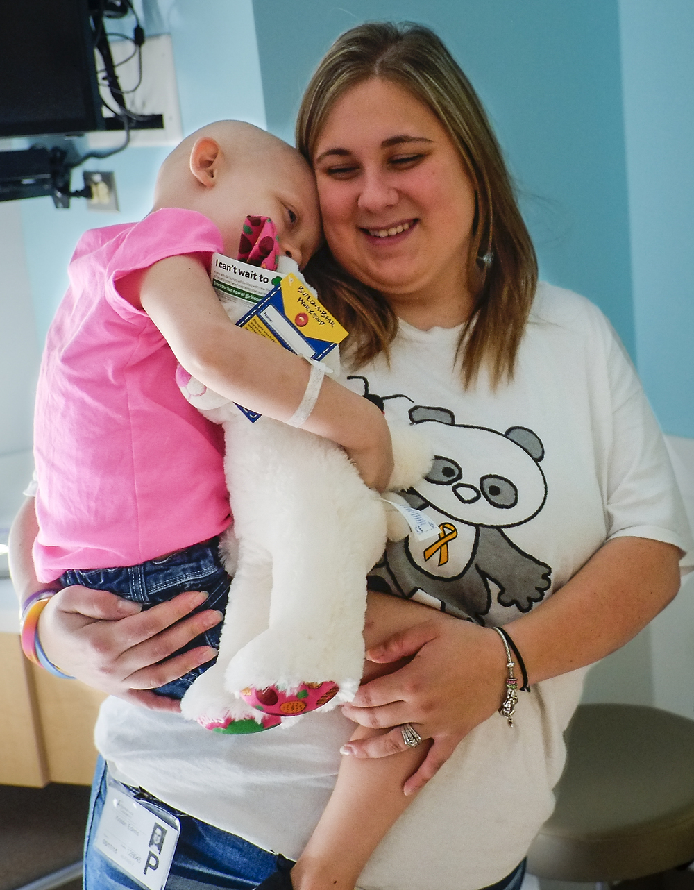 "Kristin Edens carries her daughter out of a hospital room during one of their visits to Nationwide Children's Hospital in Columbus. The sometimes weekly visits to Children's took its toll both on Alexes and her family. ""There were times where it just seemed like too much, like we were living out of a bag, but what are you going to do when your child's life is at stake?"""