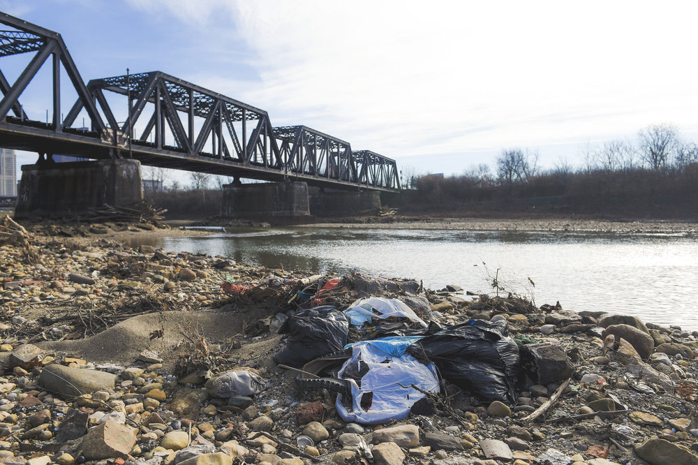 A mound of trash lay on the east shore of the Scioto River only 50 yards from the newly built Scioto Mile.