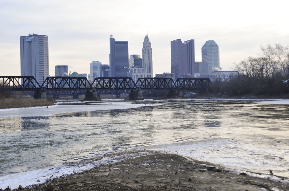Ice creeps onto the surface of the waters where the Olentangy bleeds into the Scioto River a few miles upstream from Downtown Columbus.