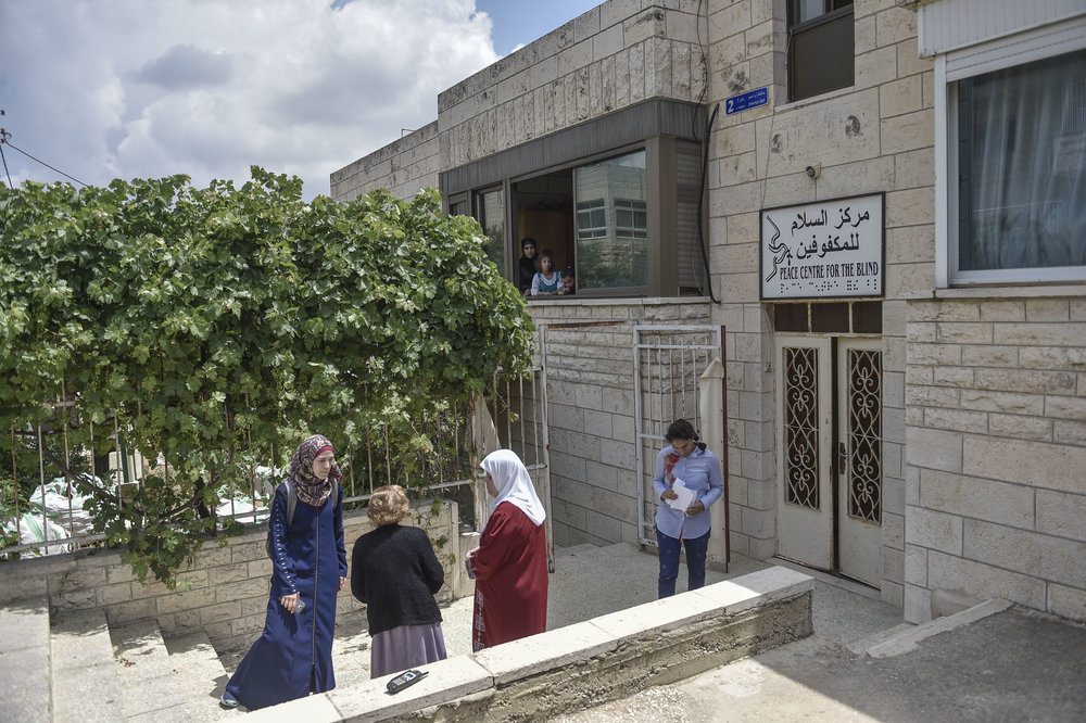 Teachers and students outside of the Peace Center for the Blind boarding house on the last day before the students return to their homes for the summer. The boarding house is rented by Miss Lydia and paid for out of funds for the school. Most of the students who attend the school and vocational training program are from the West Bank, and at the end of the school year the students return to their homes for two months.