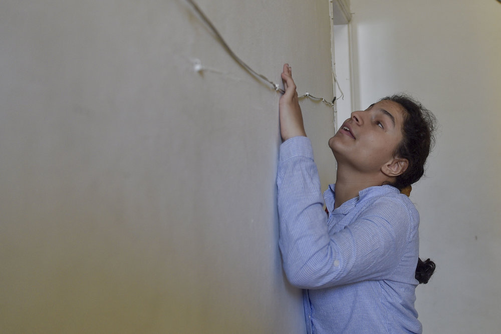 Muna Taher, 14, feels her way through a hall in the Peace Center for the Blind boarding house in East Jerusalem as she and the rest of the students prepare to return home for the summer.