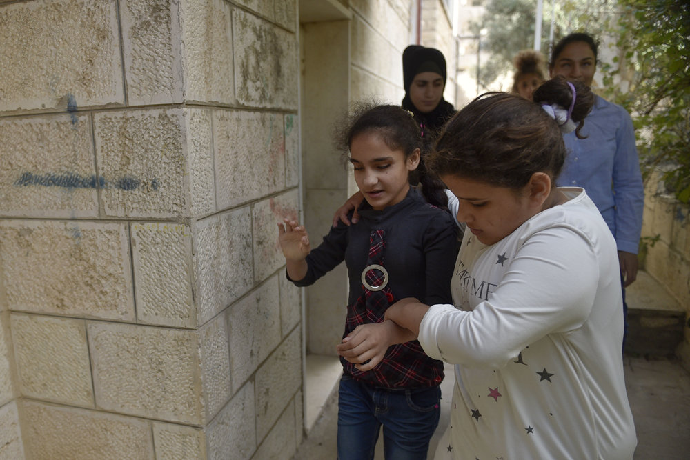 """Twelve-year-old Amira guides fourteen-year-old Snabel down the stairs outside of the boarding house for a meeting in the basement. The students grow close to each other through these school year, often helping each other when needed. """"We don't just teach academics at Peace Center for the Blind,"""" Ms. Leydia comments """"many of the students have poor social skills, and we do our best to teach them how to interact together."""""""