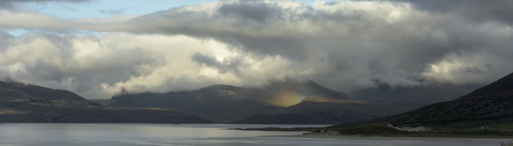 A ground rainbow bounces light upwards towards the low cloud hanging over the mountains of North Harris.