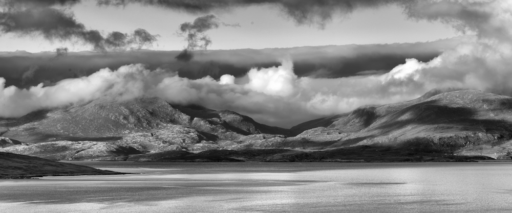 Clouds dance along the ridges of the North Harris Mountains while evening light filters through.