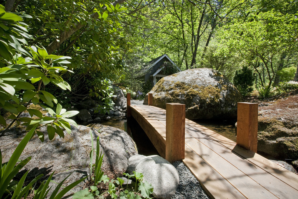 This is a small foot bridge over a creek that flows throughout the landscaping across the property