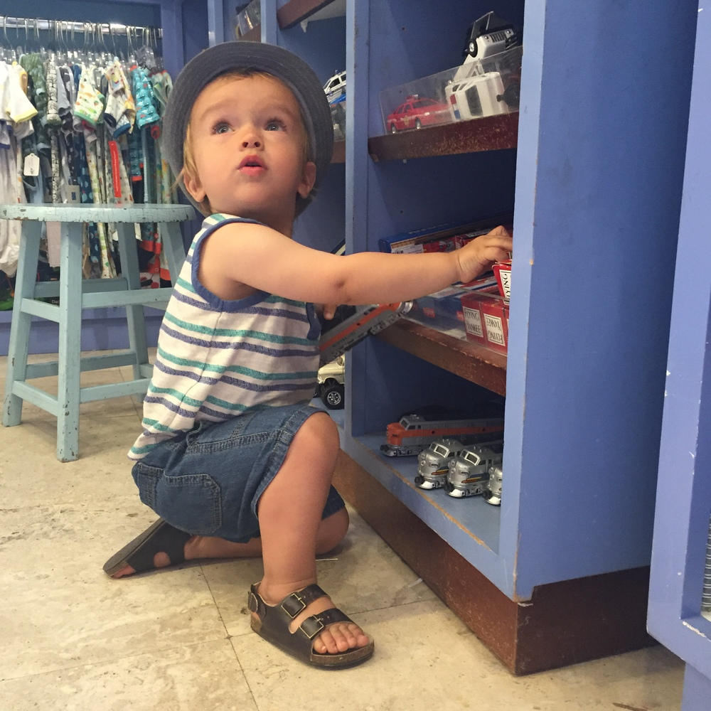 Camden loving the toys at Gigi's |  Hat  |  Top  |  Shorts  |  Sandals