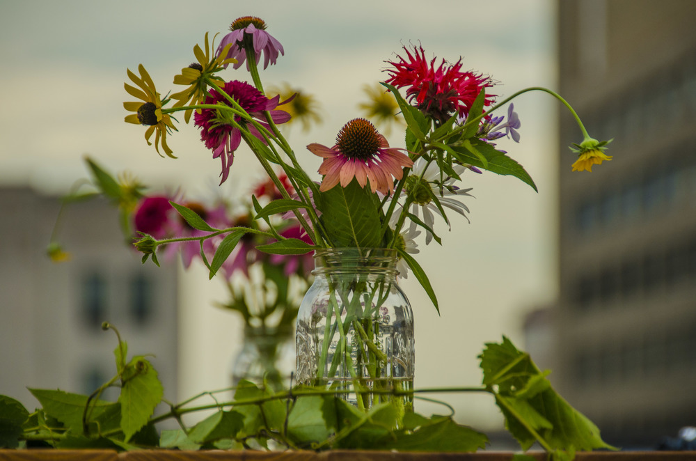 Assortment of flowers including zinnias in a mason jar