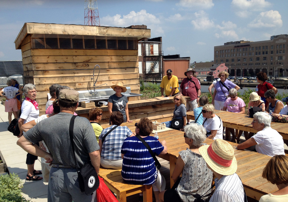 Group of elderly individuals gathered in the community hub on the FOOD ROOF Farm sitting on the picnic tables listening to executive director Mary Ostafi speak about rooftop farming