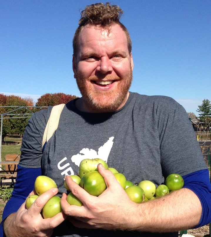 Farm Manager, Brett Hilling, smiling and holding green tomatoes from Urban Harvest's first community garden.