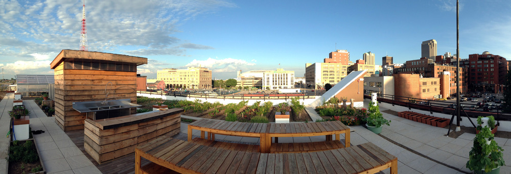 community hub space featured, wooden picnic tables and benches on raised platform, farm rows beyond with buildings of downtown st. louis in the background
