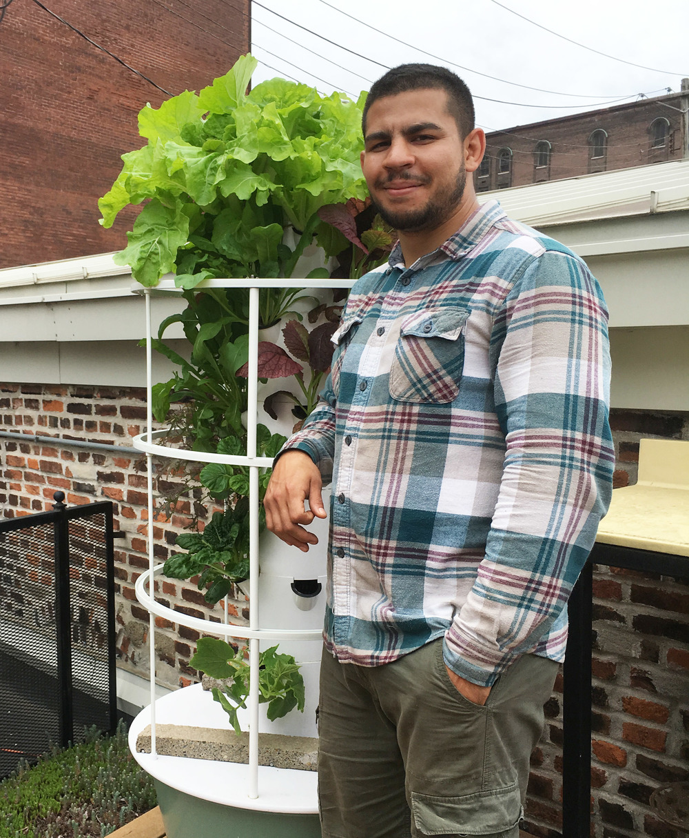 Farm worker in flannel has one hand in his pocket, smiling and leaning on a hydroponic tower on the KERR FOOD ROOF