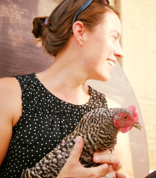 Executive Director, Mary Ostafi, middle aged woman smiling and holing a speckled chicken in the sun on the FOOD ROOF.