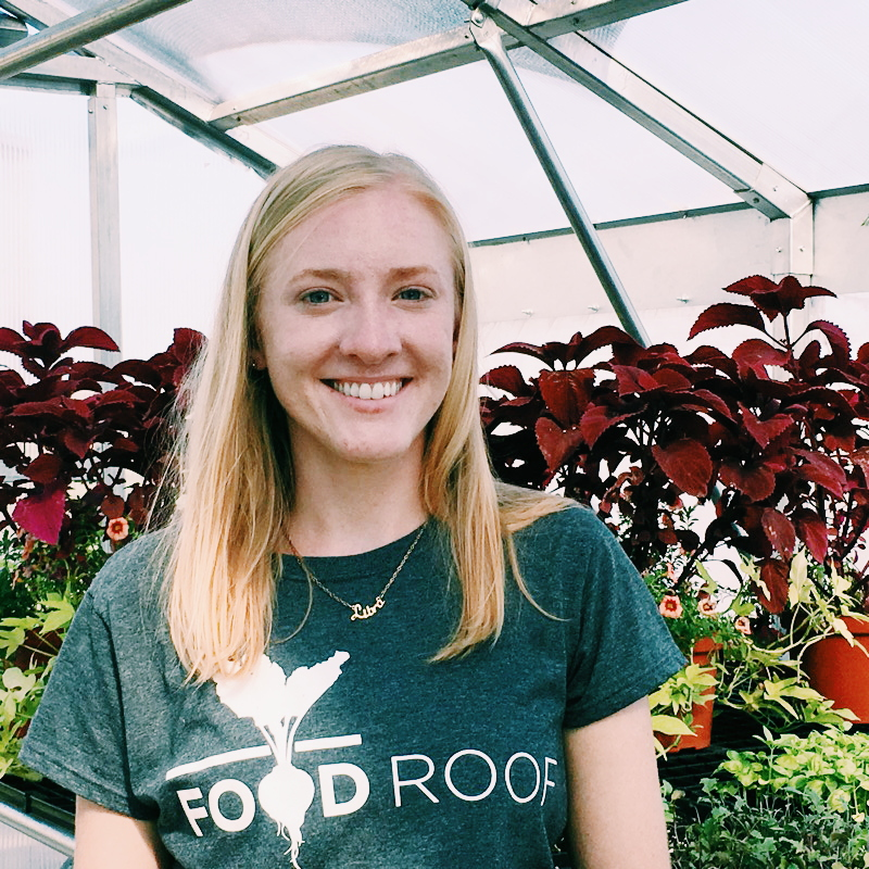 Urban Farmer, Irene Hasse, young blonde long haired woman smiling in front of red blooming plants in greenhouse on the FOOD ROOF Farm.
