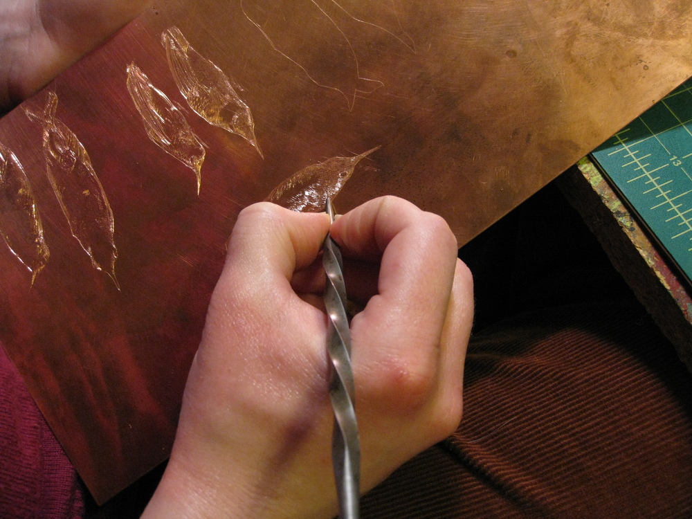 Maria using an etching needle to engrave a copper plate for an intaglio print