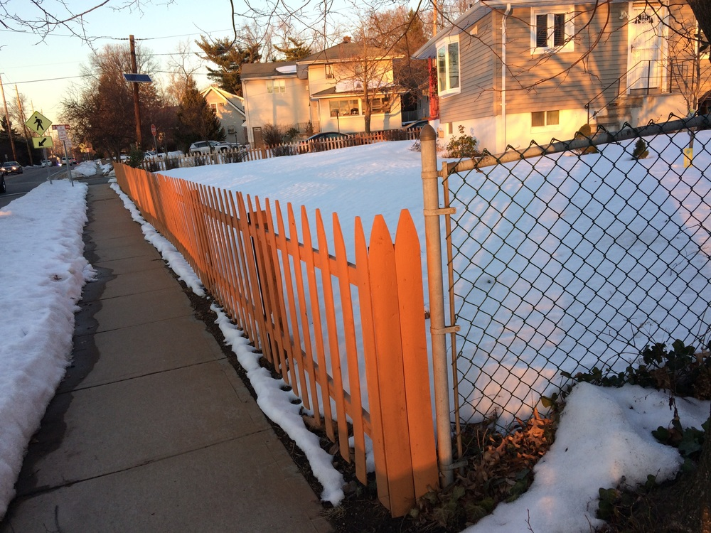 A brown fence lit gold.