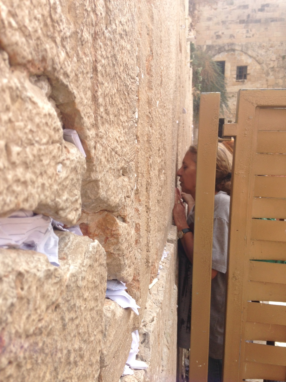 A woman praying at the Western Wall seen from the men's side.