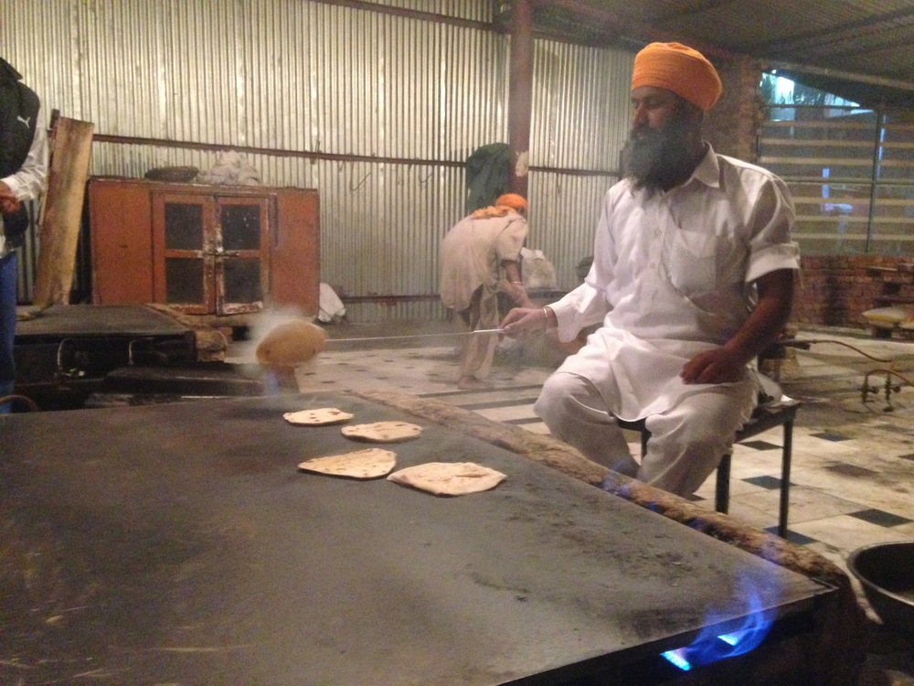 A volunteer flipping chapattis rolled out by other volunteers.