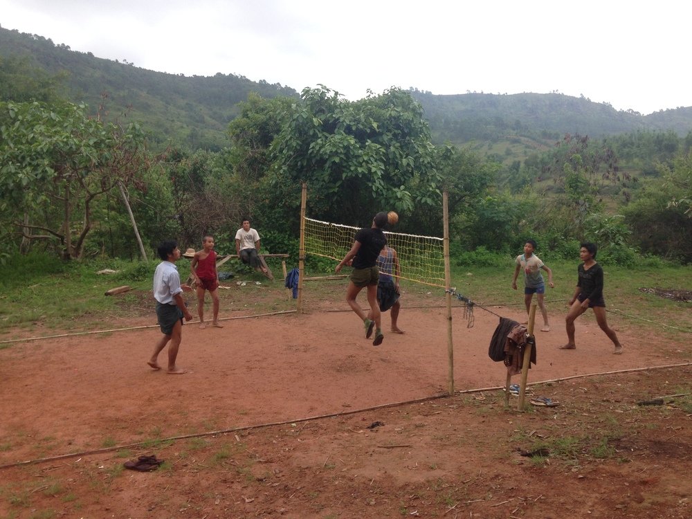 Kids playing caneball outside a village.