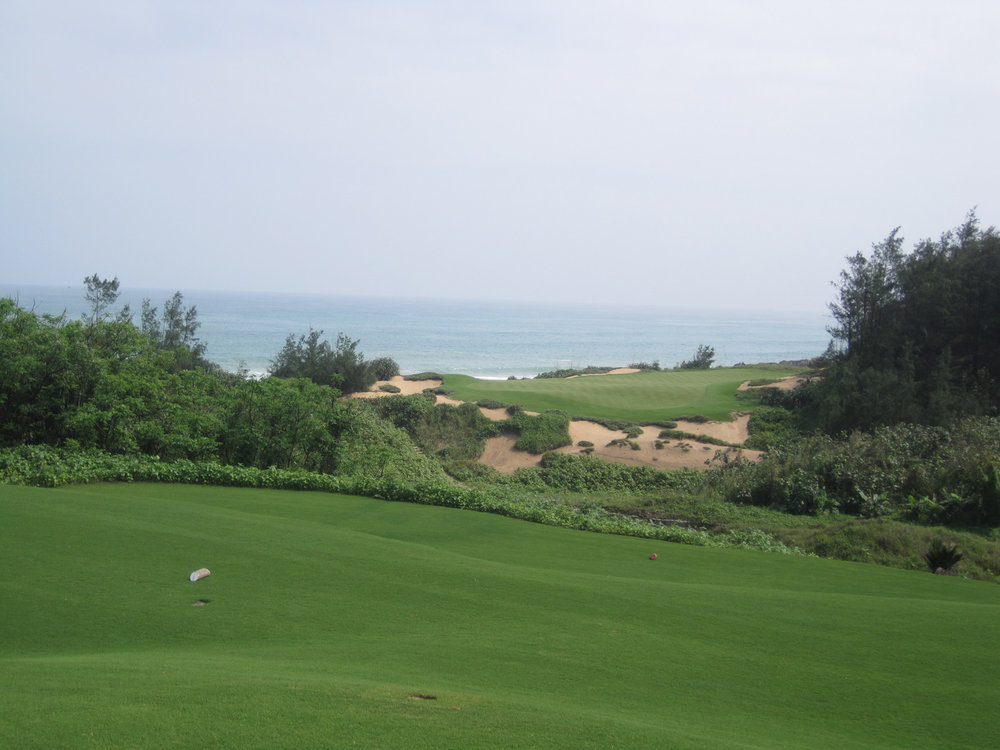 The short, 150 yard 8th hole at Shanqin Bay, South China Sea in the backdrop