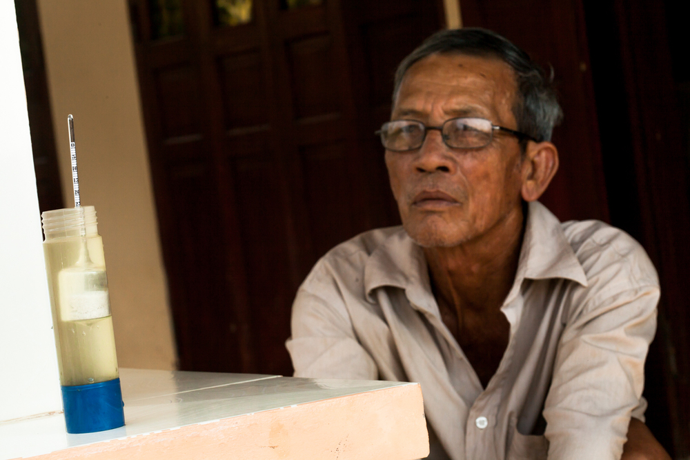 Nep, 69, looks at a test of his river water, which reads 25% saline. His shrimp farm is currently inoperable due to such high levels.