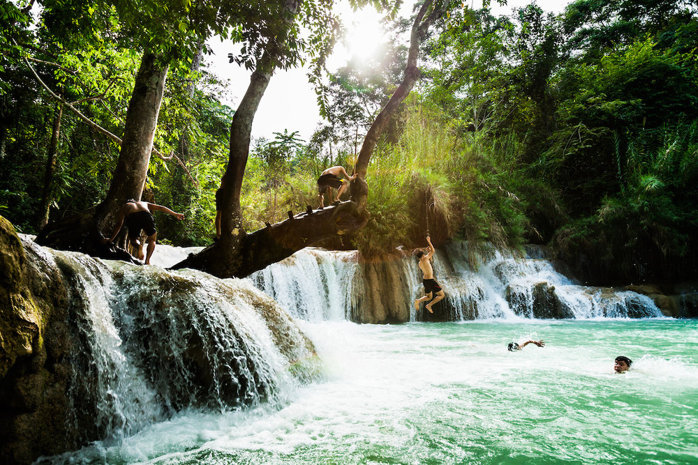 Local teens play on the rope swing at Kuang Si falls in Luang Prabang, Laos.  This was my third visit to the falls and I'd clambered up that tree and flung myself in many times.  With the sun blasting through and the waterfall raging these scene was perfect for a great photo.  These boys turned up and they where having a blast so I waded in and framed the scene up and then waited for the decisive moment.   Canon 5D Mk II, 16-35mm f2.8L lens at 23mm, 1/320 sec at f5.6, ISO 400.