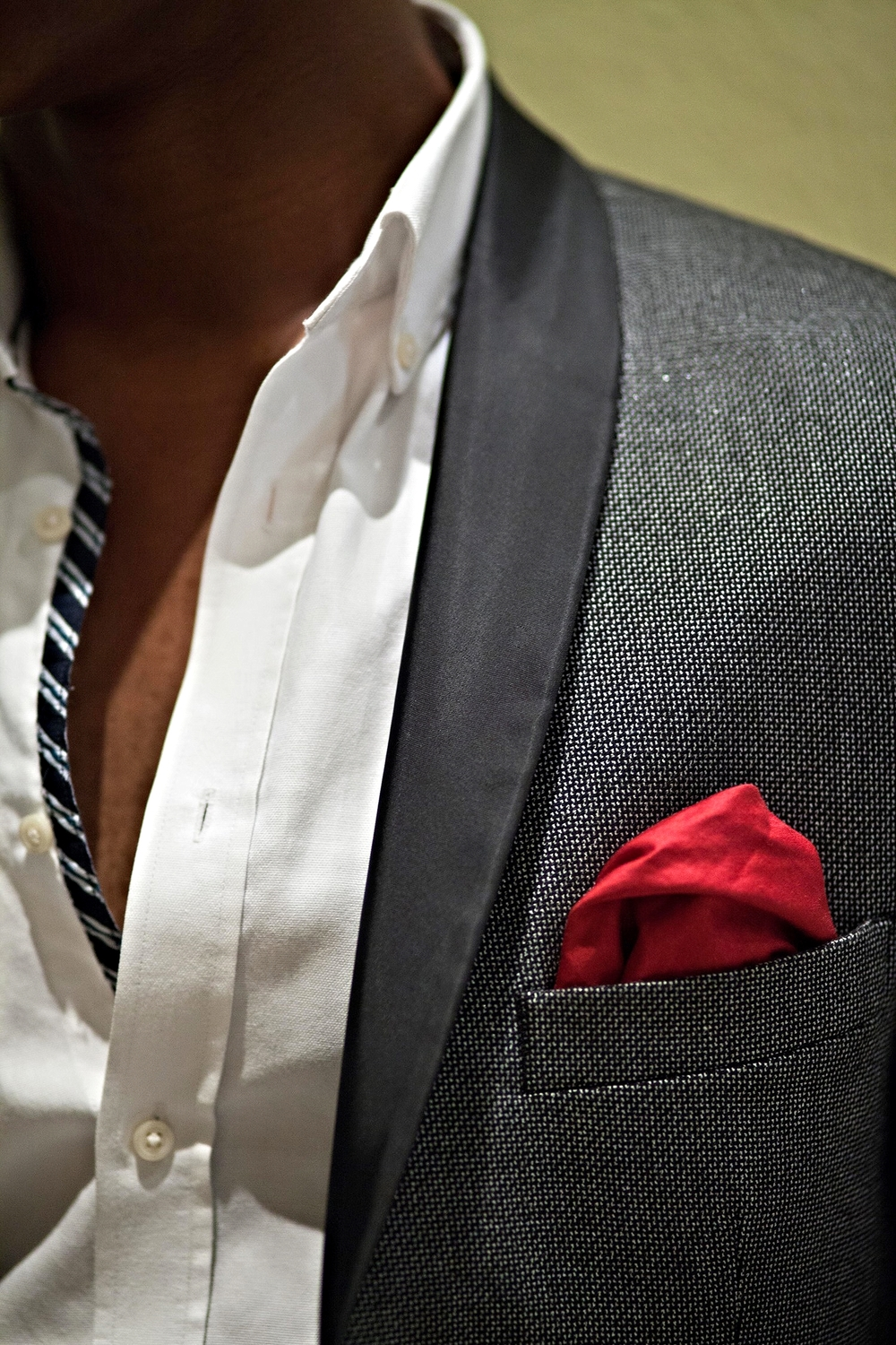 A red pocket square usually goes with any suit color . It is the right amount of color to bring life to a charcoal ,tweed suit like this one