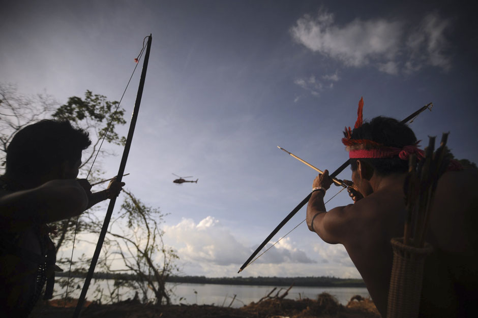 """They made us many promises,but they kept only one; they promised to take our land, and they did."" -Chief Mahpina Luta aka Red Cloud(1822-1909)      Indigenous people point their bows and arrows at a police helicopter flying over the occupied barrier of the Belo Monte Dam's construction site in Vitoria do Xingu, near Altamira in northern Brazil June 15, 2012.  (via  Best photos of the year 2012 