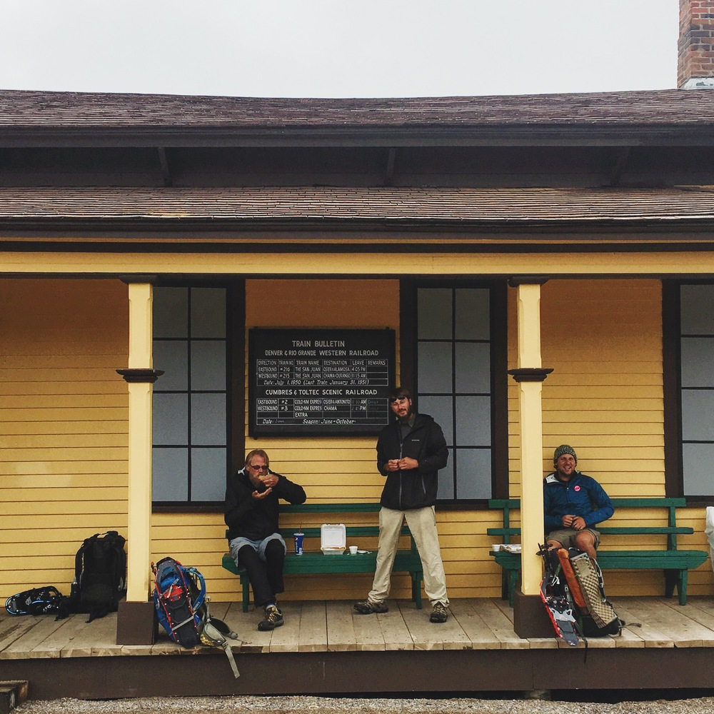 Lodgepole, Maverick, and Banjo eat town snacks at the Cumbres Pass train station before braving the elements again.